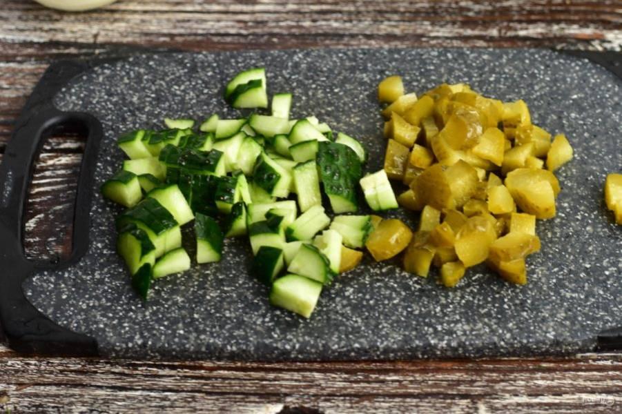 Нарежьте соленый и свежий огурец.