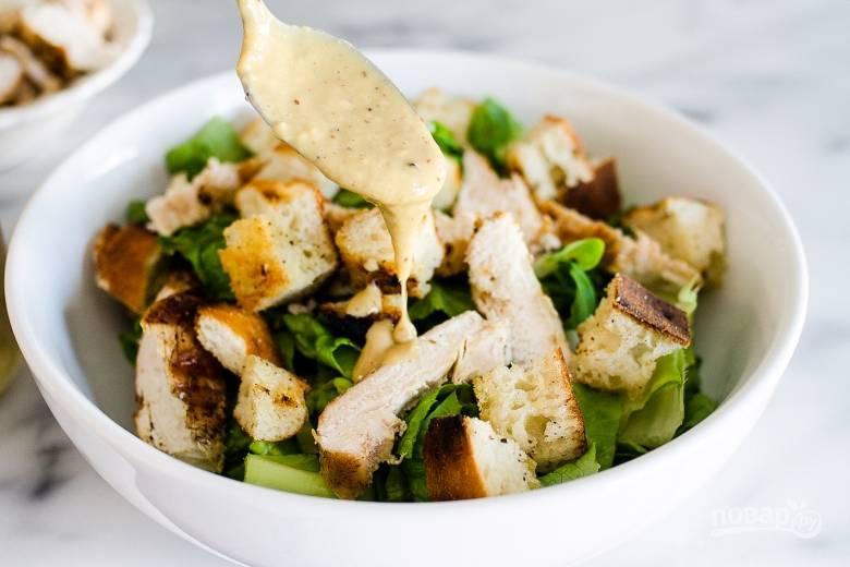 В салатницу нарвите промытый латук. Сверху выложите сухари и курицу. Залейте соус.