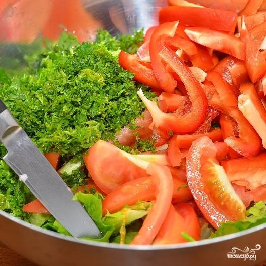 В большую миску шинкуем зелень, туда же добавляем крупно нарубленные листья салата, а также нарезанные дольками помидоры и тонкими пластинками перцы.