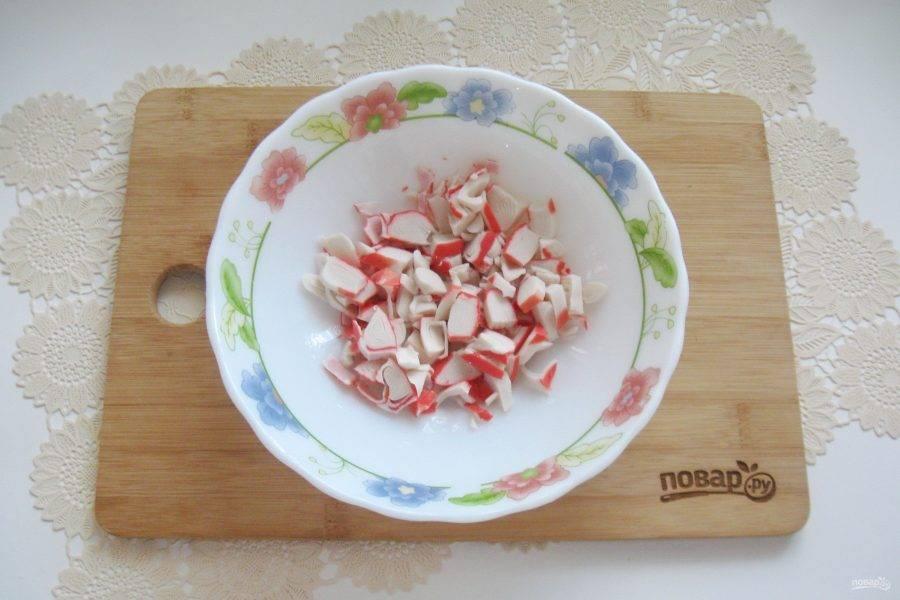Крабовые палочки нарежьте и выложите в салатник.