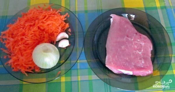 Подготавливаем необходимые продукты: лук и мясо нарезаем кубиками, чеснок пластинками, а морковь трем на крупной терке.