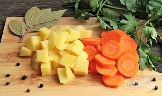 1. Семгу вымойте, обсушите немного, выложите в кастрюлю с водой и поставьте на огонь. Добавьте очищенную луковицу. После закипания уберите огонь до минимума и варите около 15 минут. За это время очистите и нарежьте кубиками картофель, кружочками — морковь.