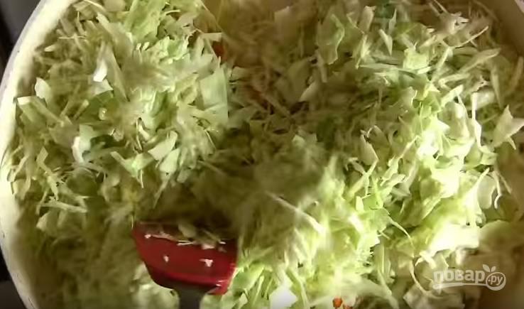 3. Через 2-3 минуты отправьте в сковороду нашинкованную капусту, перемешайте. Тушите около 15 минут, добавив соль, черный перец и немного воды.