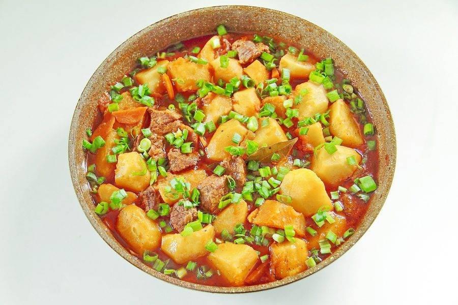 7. Накройте сковороду крышкой и на небольшом огне продолжайте тушить жаркое около 10 минут, пока картофель не станет мягким. Готовое блюдо обильно посыпьте рубленным зеленым луком.