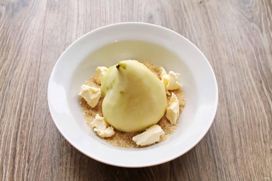 В миску, пригодную для приготовления в микроволновке, всыпьте коричневый сахар и установите грушу, срезанной стороной вниз. Масло разрежьте на кусочки и выложите вокруг груши.