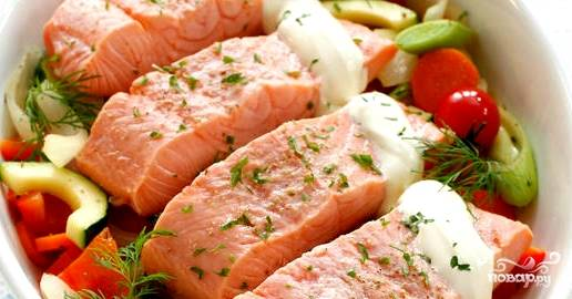 Берем форму для запекания. Выкладываем в нее овощи. Сверху кладем замаринованную рыбу. Поливаем оставшимся соком от маринада. На рыбу выдавливаем сметану. Присыпаем специями.