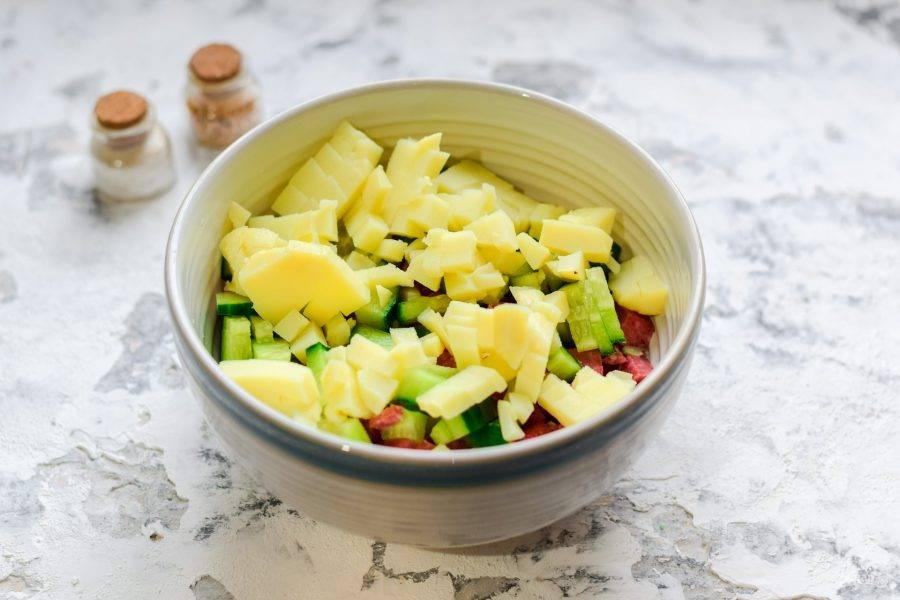Вареный картофель нарежьте небольшими кубиками, добавьте в миску ко всем ингредиентам.