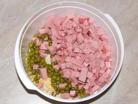 Мелкими кубиками нарезаем вареную колбасу и добавляем ее в салатницу.