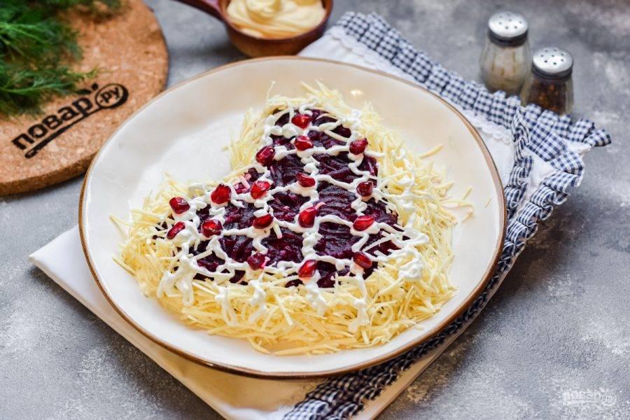 Твердый сыр натрите на мелкой терке и выложите по краям салата. Украсьте салат майонезом и зернами граната. Подавайте салат к столу.