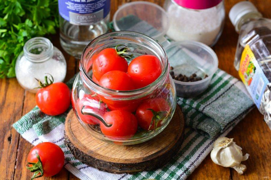 Выложите в банку промытые помидоры.