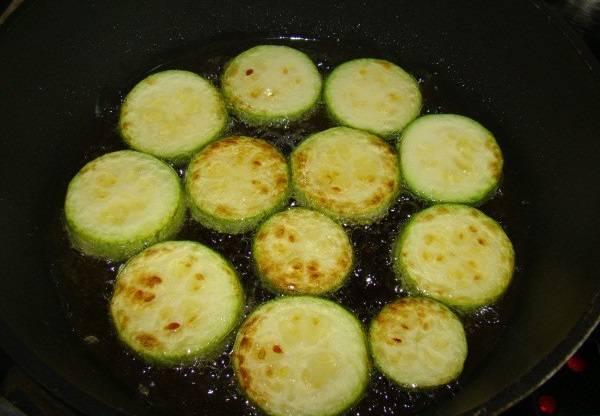 2. Посолить немного кабачки по вкусу и отправить на сковороду с разогретым растительным маслом. Обжарить с двух сторон до аппетитной корочки и выложить на бумажное полотенце, чтобы убрать лишний жир.