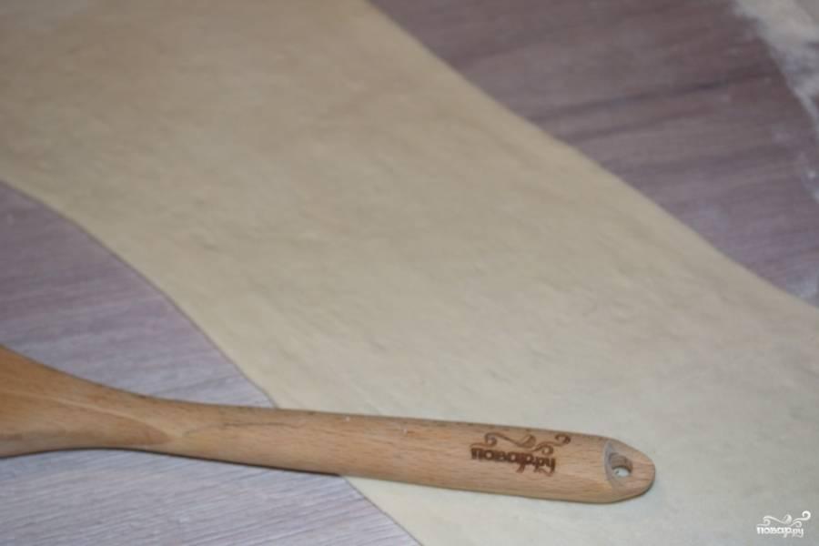 Для приготовления сосисок в слоеном дрожжевом тесте нам необходимо взять тесто. Разморозьте его и слегка раскатайте на присыпанном мукой столе.