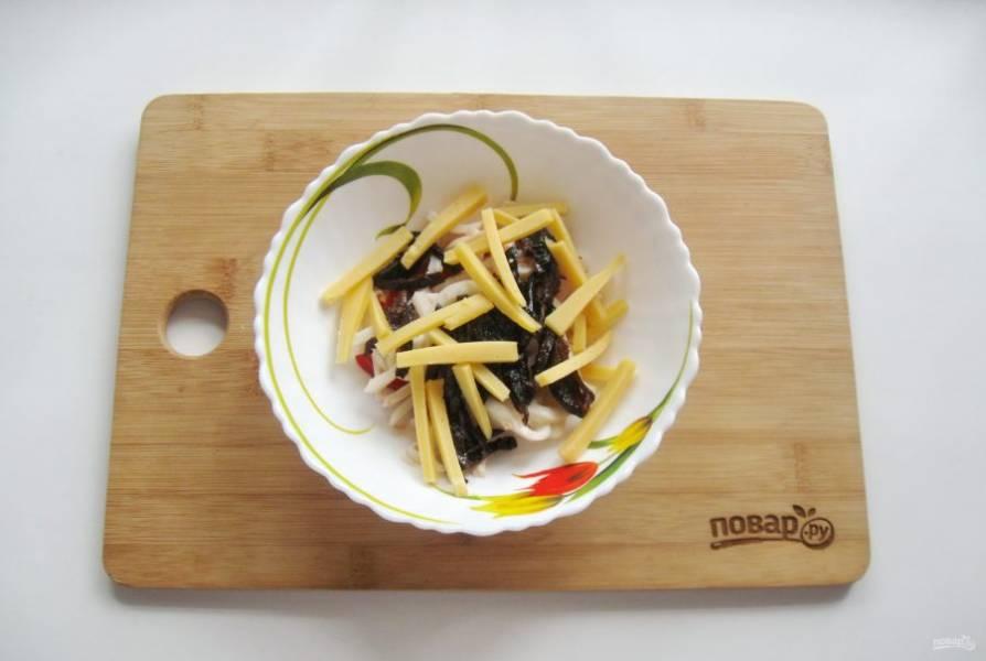 Твердый сыр также нарежьте соломкой и выложите в салат.