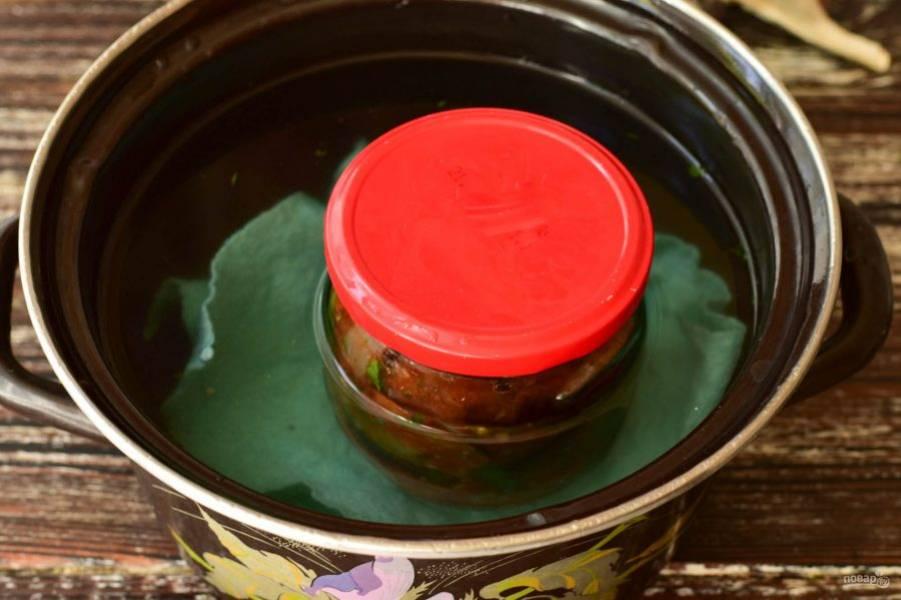 В кастрюлю налейте теплую воду, выложите тряпку, установите банку с баклажанами, прикройте ее крышкой. Стерилизуйте овощи в течение 3-5 минут. Если они будут сразу же подаваться к столу, а не закатываться на зиму, тогда данную процедуру можно пропустить.