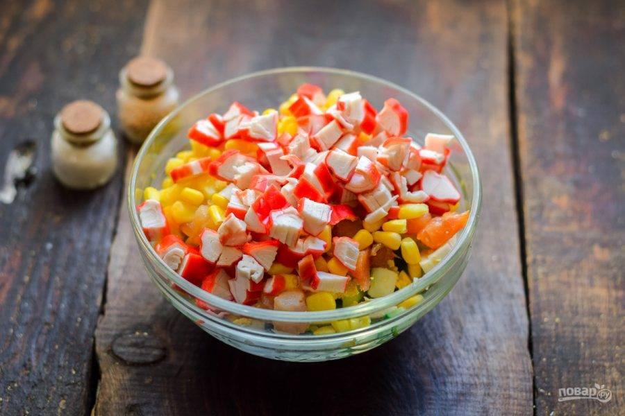 Крабовые палочки нарежьте кубиками и добавьте ко всем ингредиентам.
