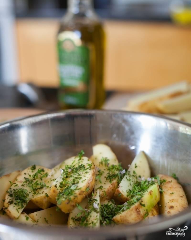 Нарежьте картофель дольками и посыпьте зеленью. Выложите в форму для запекания. Поставьте в духовку за 20 минут до того, как приготовятся рёбрышки. Увеличьте огонь до 220 градусов. Картофель и рёбрышки подойдут одновременно.