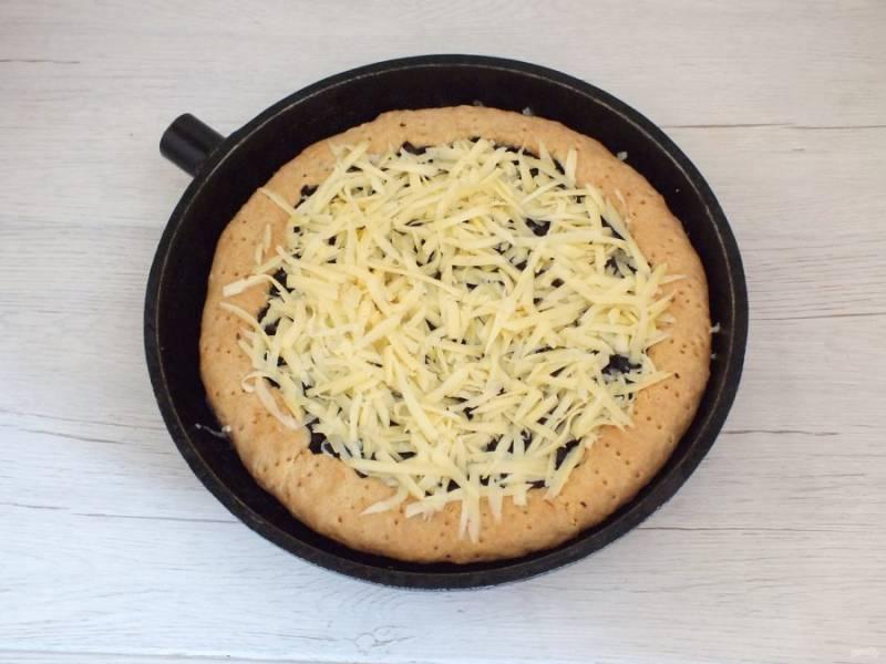 Когда пирог будет готов, достаньте его из духовки. Сверху присыпьте тертым сыром и поставьте в духовку, чтобы сыр расплавился.