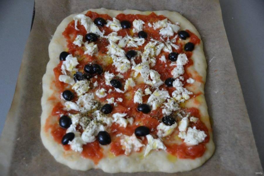 На подпеченную основу пиццы выложите томатную пассату или помидоры в собственном соку, выложите моцареллу, маслины, посыпьте сухими травами. Снова отправьте в духовку на 10 минут.