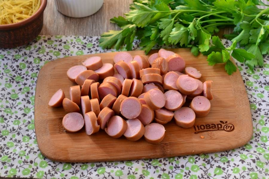 Сосиски порежьте кружочками и обжарьте вместе с луком и морковью всего пару минут.