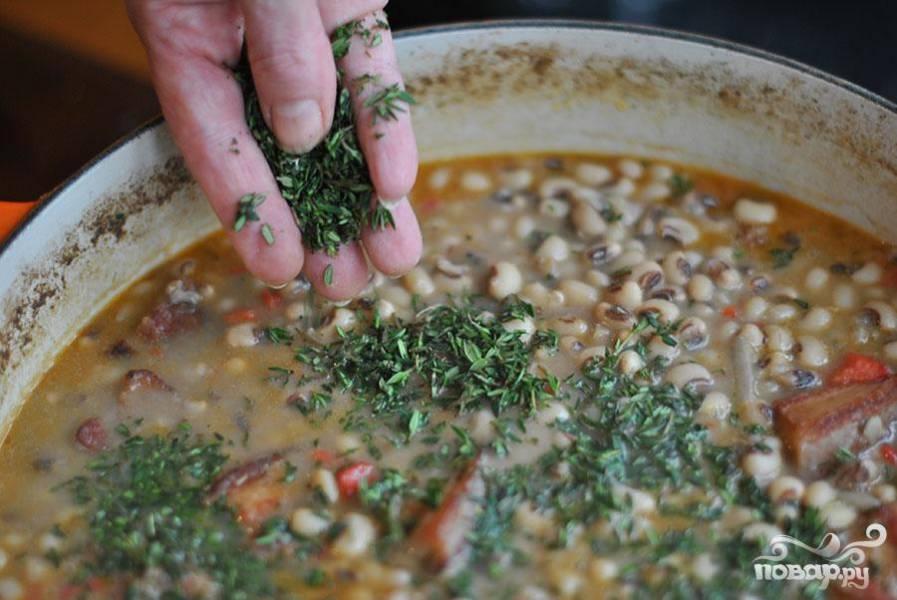 4. Когда фасоль полностью размягчится, хорошо приправить суп солью и перцем и добавить измельченный тимьян. Продолжать варить еще пару минут. Подавать суп с нарезанным красным луком и уксусом или перечным соусом на тарелке.