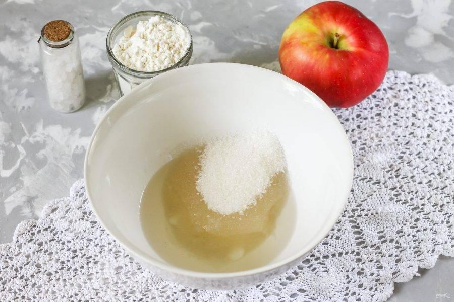 Кокосовое масло растопите в микроволновке, выложив его в глубокую емкость. Всыпьте в емкость сахар и соль, тщательно перемешайте. По желанию кокосовое масло можно заменить сливочным или маргарином. 2 ст.л. сахара оставьте для присыпки яблок.