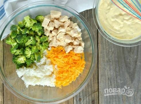 Заранее отварите рис, брокколи, морковь и курицу до готовности. Затем разберите брокколи на соцветия, морковь натрите на крупной тёрке, а курицу нарежьте кубиками.