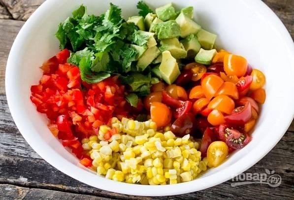 2. Нарежьте помидоры четвертинками, кубиками очищенное авокадо и перец. Соедините все с кукурузой и измельченной зеленью.