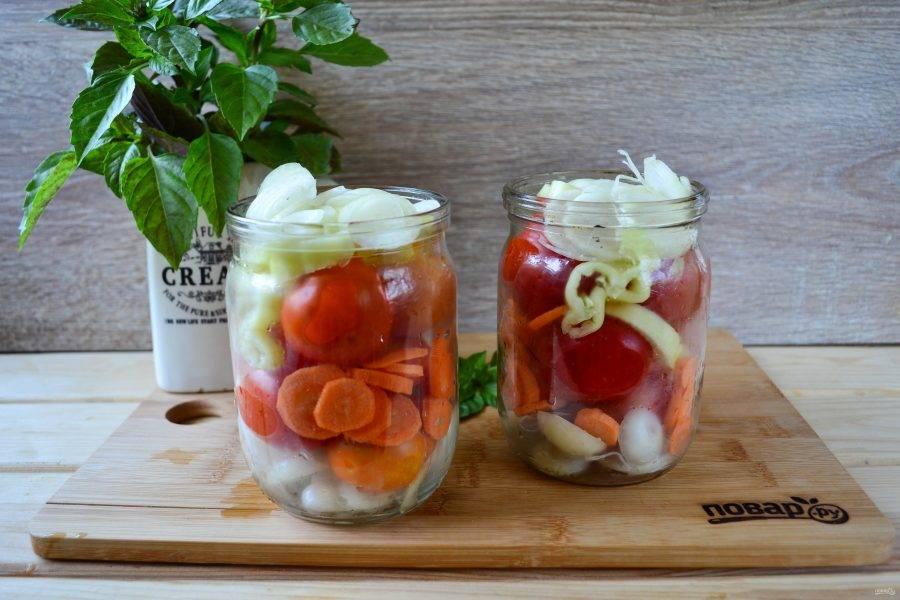 Простерилизуйте баночки, затем на дно положите половину лука, помидоры, сладкий перец, морковь и снова лук (можно и в другом порядке). Также в баночки положите по несколько листиков свежего базилика и по щепотке итальянских трав. Благодаря этому закуска получится невероятно ароматной.