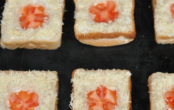 Сверху кладем хлеб без мякиша ,в серединку кладем кусочки помидора. Смазываем еще майонезом и присыпаем тертым сыром.
