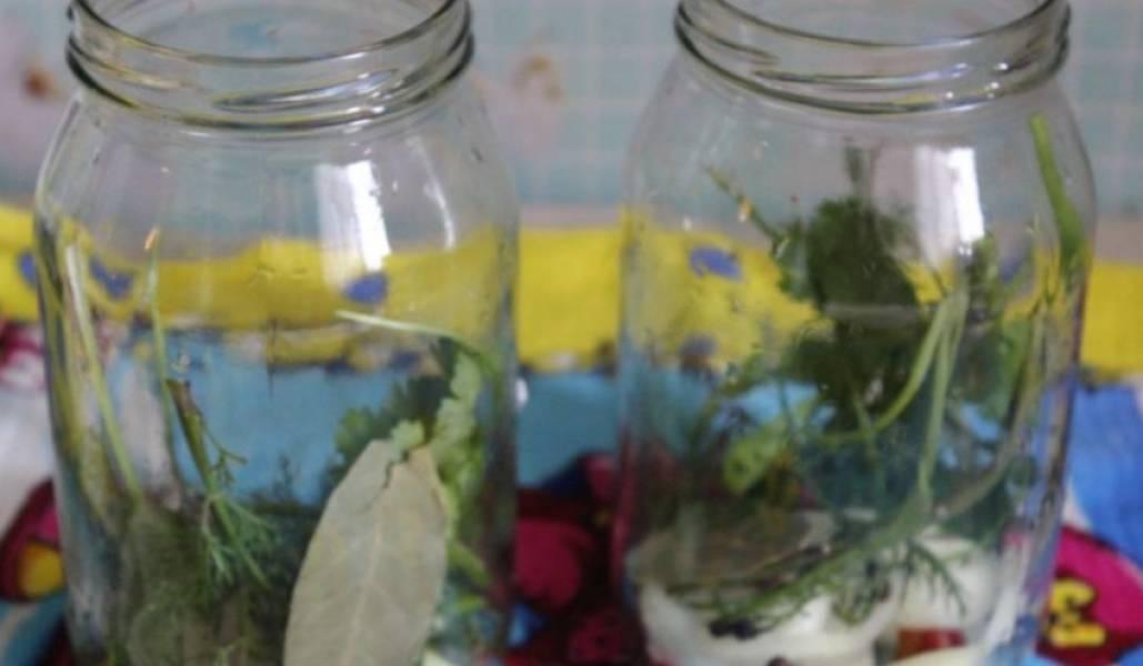На дно двух чистых банок (по 1 л.) раскладываем острый перец и лук, порезанные колечками. Также кладем перец горошком, измельченную кинзу, лавровые листы и зубчики чеснока.