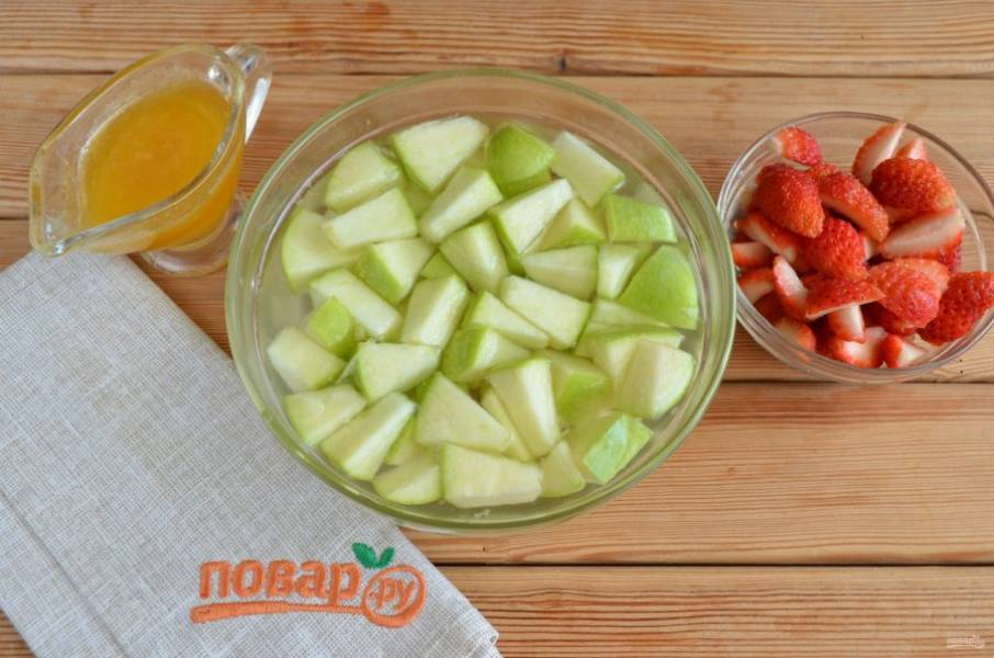 Подготовьте фрукты для пиццы. Удалите сердцевинку яблока, порежьте на кусочки небольшого размера, сбрызните лимонным соком или замочите в лимонной воде их на пару минут. Если нет лимона, можно  развести в холодной воде пару щепоток лимонной кислоты, эффект будет тот же. У клубники оборвите хвостики и порежьте на 4 части.