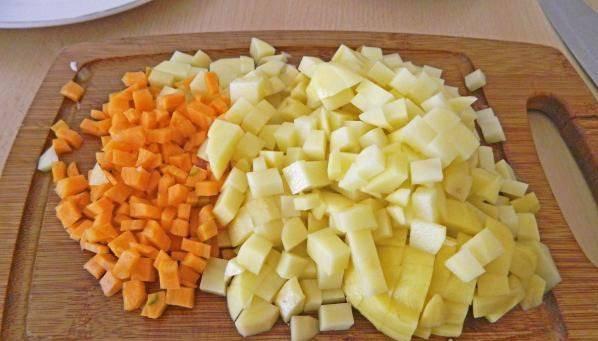 Картофель и морковку нарезаем кубиками. Высыпаем все в кастрюлю, заливаем горячей кипяченой водой. Ждем пока закипит.