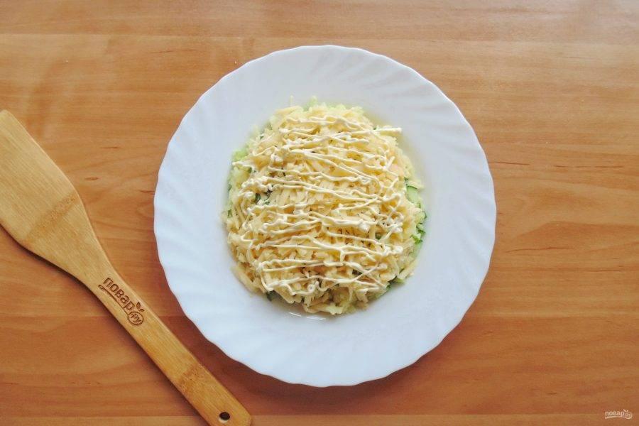 Любой твердый сыр натрите на терке и выложите на зеленый лук.