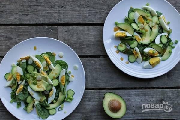 И собираем салат. Выкладываем шпинат, дольки авокадо и яйца, кружочки огурца. Поливаем заправкой. Можно добавить немного зеленого лука.