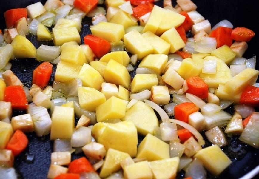 Картофель нарежьте кубиками и добавьте на сковороду. Посолите, добавьте измельченный чеснок и специи по вкусу. Протушите вместе минут 7.