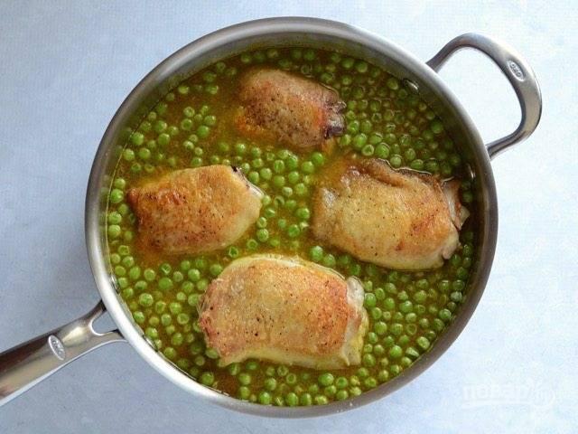 6.Выложите куриные бедра в сковороду к рису и горошку, поставьте ее на средний огонь и доведите до кипения.