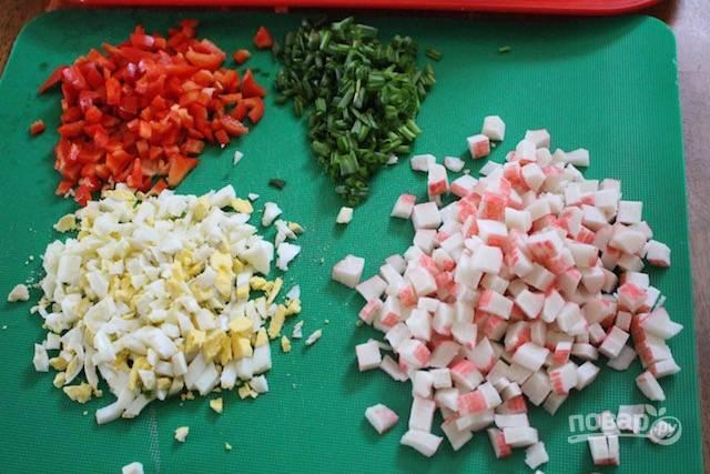 Мелко нарежьте яйца вместе с перцем, луком и крабовыми палочками.