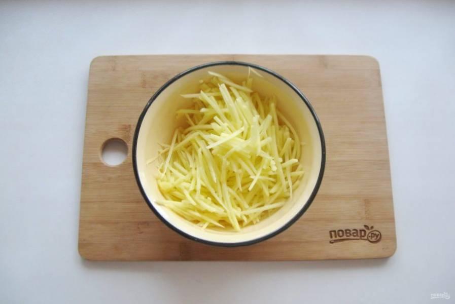 Приготовьте картофельную соломку. Для этого картофель очистите и натрите на терке для корейской моркови. После хорошо помойте в воде, удаляя крахмал.