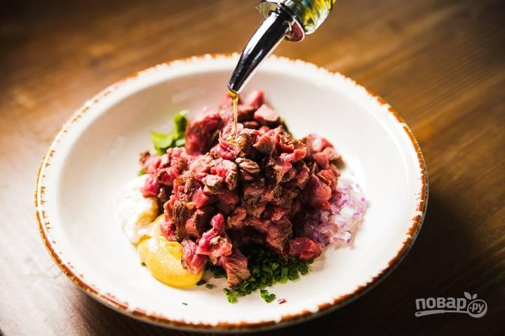 Готовое мясо нарежьте кубиком и добавьте к овощам. Полейте все оливковым маслом, приправьте солью и перцем, перемешайте.