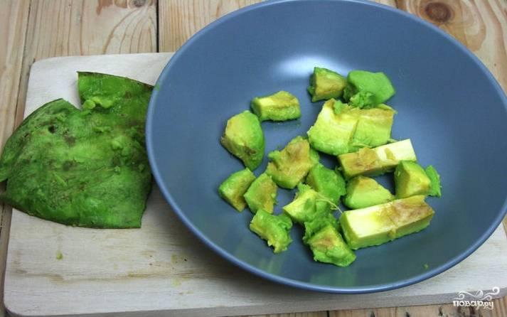 Снимите с авокадо шкуруку, аккуратно разрежьте его на две части, доходя до косточки. Затем достаньте косточку и нарежьте авокадо небольшими кубиками. По желанию нарезать его можно и продолговатыми дольками.