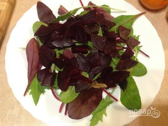 Очистим свеклу и нарежем тонкими пластинками. Выложим на листья салата.