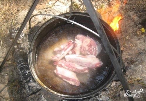 Мясо порубить крупно и положить в казан с водой.