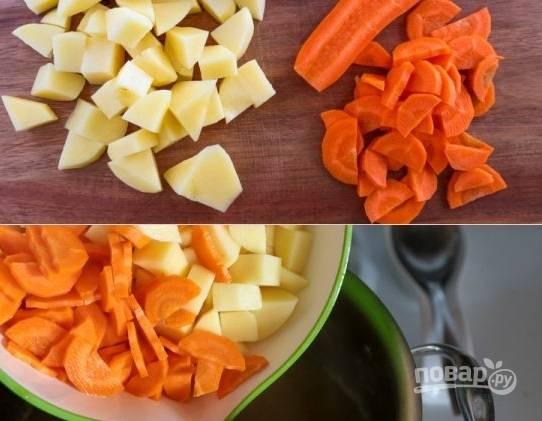 2. Часа через полтора очистите и нарежьте средними кубиками картофель и половину моркови. Выложите в кастрюлю и варите минут 15.