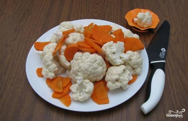 Очистите и промойте цветную капусту. Разделите ее на соцветия. Очищенную морковку промойте и нарежьте тонкими полукругами.