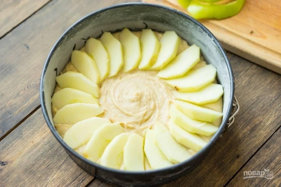 Разогреем духовку до 175 градусов. Форму для выпечки смажем сливочным маслом, а затем выложим туда тесто, а наверх красиво уложим дольки яблок. Присыплем яблоки корицей и небольшим количеством сахара. Ставим в духовку.