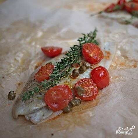 Рыбу хорошенько натираем солью и перцем. Берем пергаментную бумагу, наливаем на край бумаги немножко оливкового масла, кладем на масло рыбу. Под рыбу кладем пару тонких ломтиков лимона, на рыбу - веточки тимьяна, а также обжаренные каперсы, помидоры и чеснок. Сверху еще раз слегка сбрызгиваем оливковым маслом.