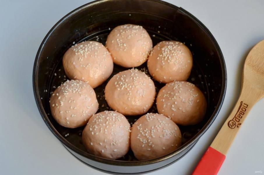 8. Смажьте форму маслом растительным. Положите булочки, смажьте их молоком  и посыпьте кунжутом. Оставьте в тепле на 20 минут для расстойки.