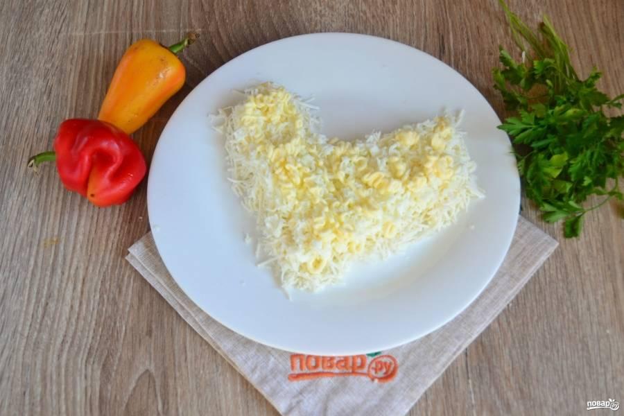 Сверху выложите половину яичных белков и снова смажьте майонезом.