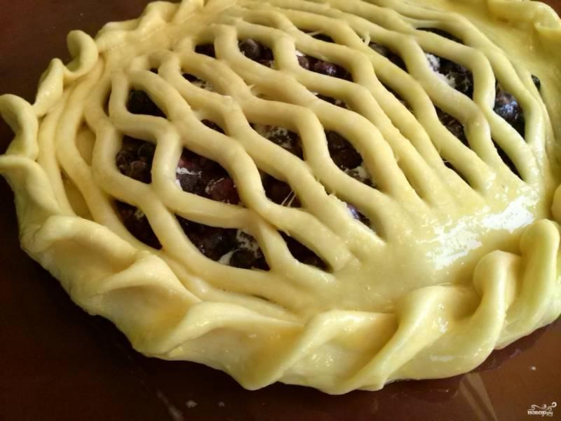 Получившуюся сетку немного растяните по диаметру начинки и положите сверху нее. Защипните края нижней лепешки, поднимая их сверху сетки. Сформируйте второй пирог. Накройте пироги, оставьте его отдохнуть на полчаса. При желании можно смазать верх пирога взбитым яйцом.