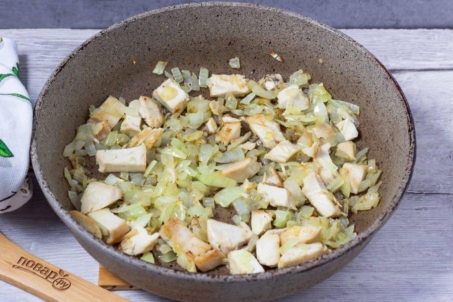 Куриную грудку обжарьте на оливковом масле до готовности, затем добавьте нарезанный лук. Жарьте ещё 2-3 минуты.